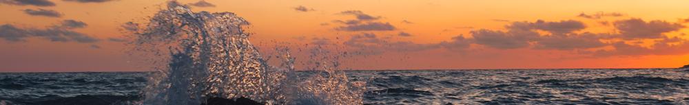 wave splashing on rock at sunset photography